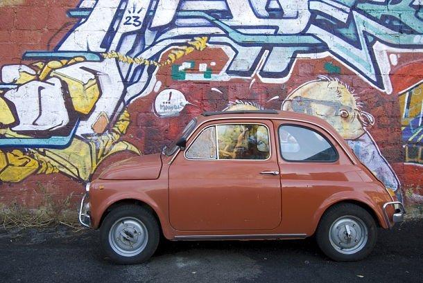 Petite voiture italienne traditionnelle contre des graffitis contemporains ©Shutterstock/pippa west
