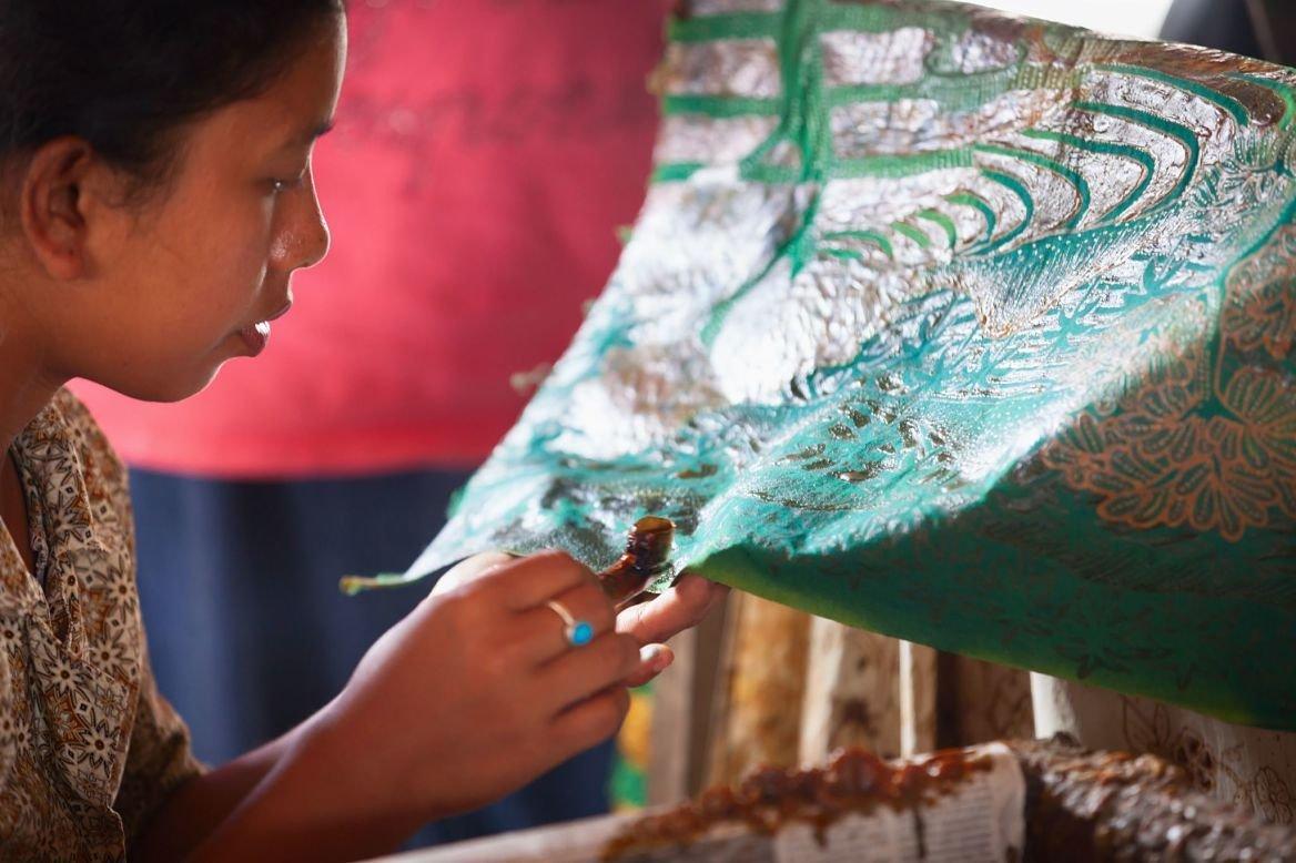 Femme balinaise appliquant de la cire sur un bout de batik, Bali